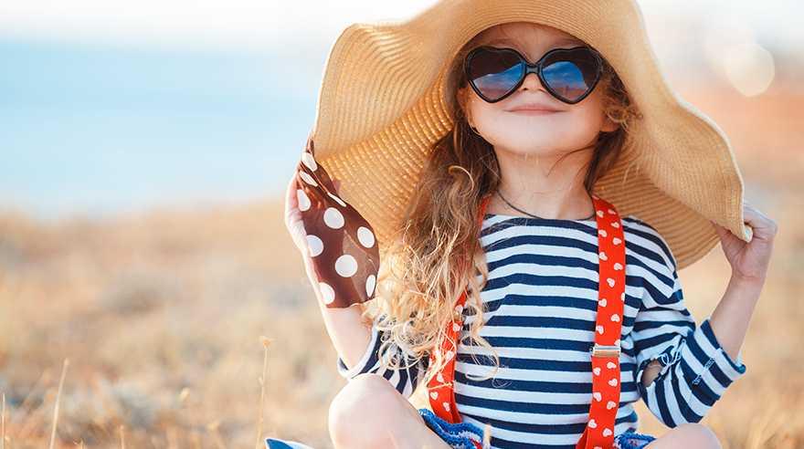 mergaitė su skrybėle ir akiniais nuo saulės
